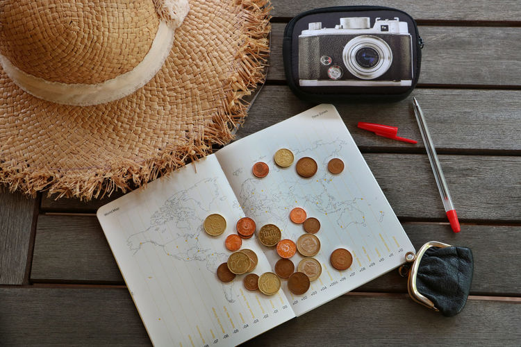 High angle view of coins with map and hat on table
