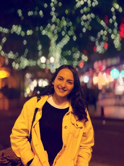 Portrait Of Smiling Young Woman Standing In Illuminated City At Night