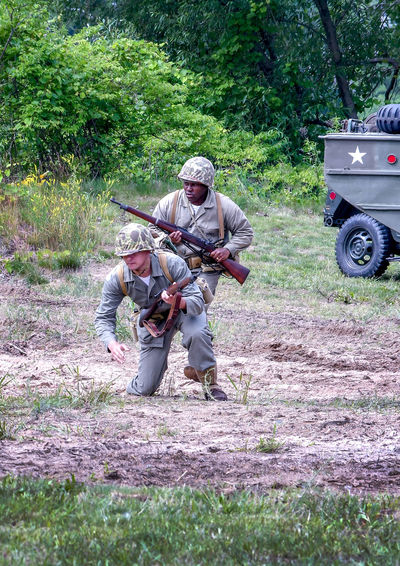 June 22 2018 St Joseph MI USA ; two sildiers run for coverduring a war reenactment in Michigan USA Acting American Military Event Field Fight Korean War Lest We Forget Nature Soldiers Uniforms Active Adults America Editorial  Historiacl Reenactment History Men Military Outdoors People Reenactment Role Playing St Joseph MI USA Vintage Uniforms War Weapons