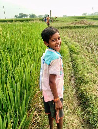 Full length of smiling girl standing on field