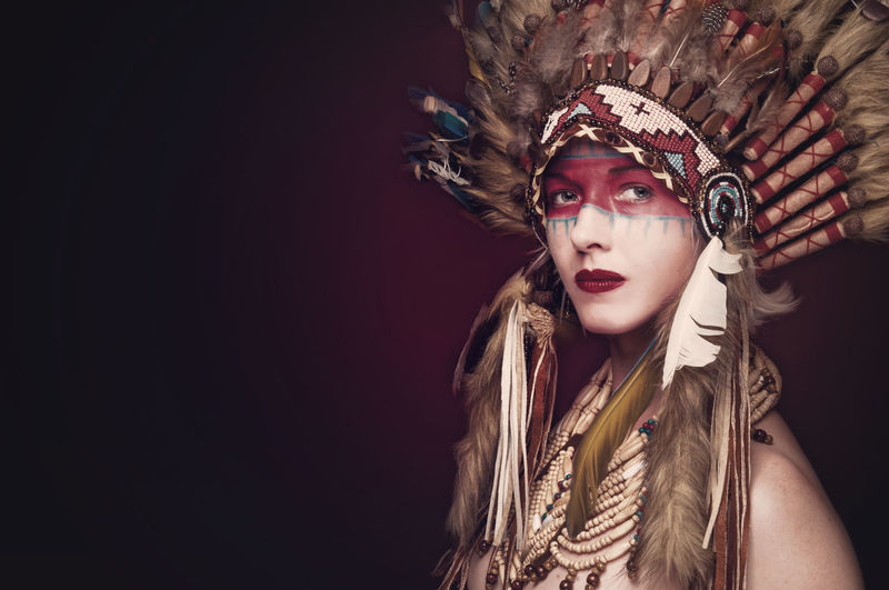 Portrait of young woman wearing headdress against colored background