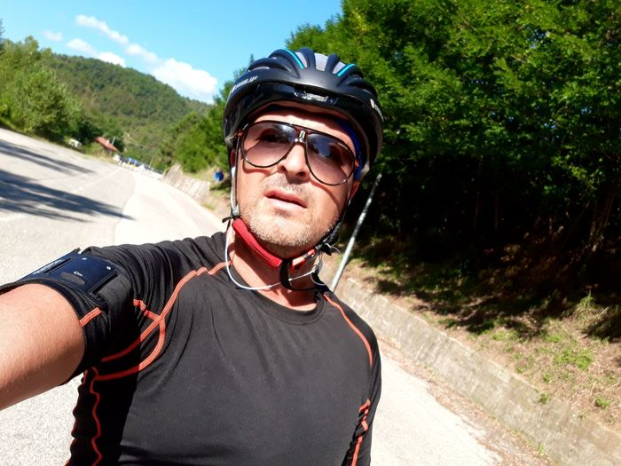 Portrait Of Man Wearing Cycling Helmet And Sunglasses On Road During Summer