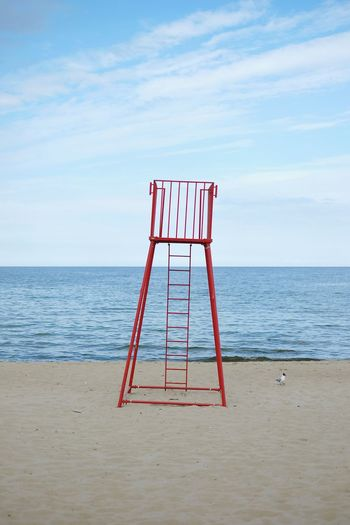 Empty lifeguard chair and seagull on beach