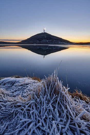 Scenic view of frozen lake against clear sky during sunset