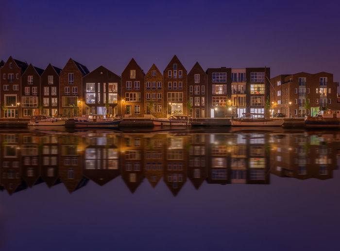 Buildings reflecting on lake in city at dusk