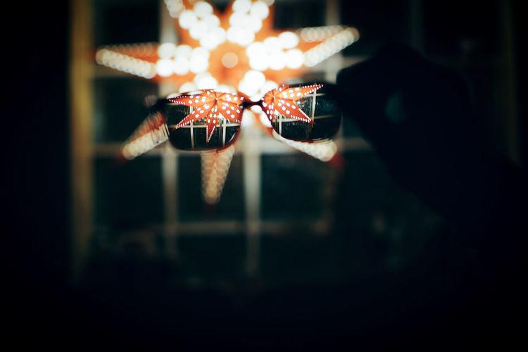 Close-up of hand holding eyeglasses against illuminated christmas lighting equipment