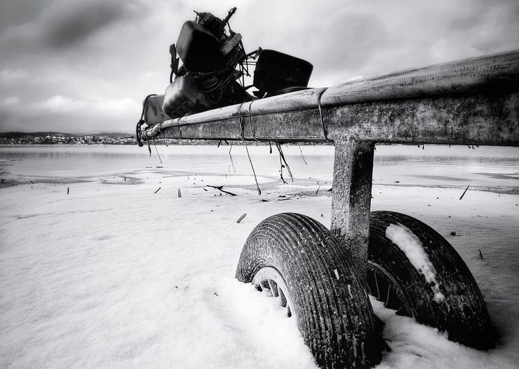 Damaged boat moored on beach during winter