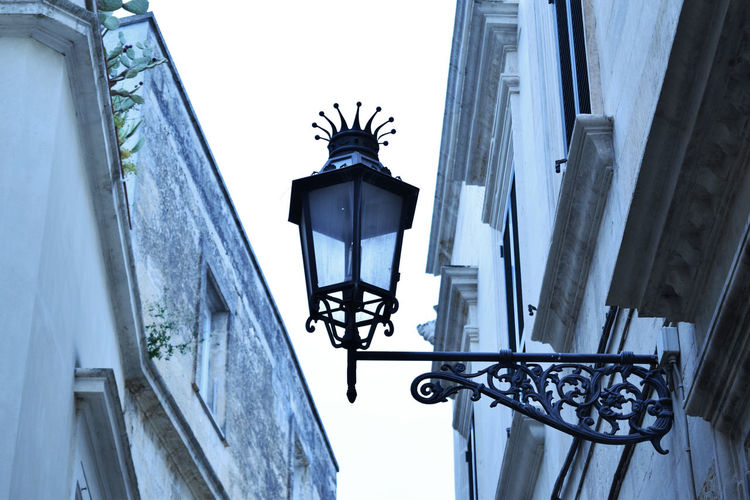Low angle view of street light on building against sky