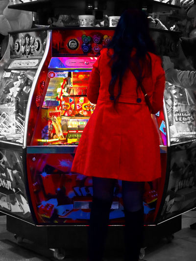 One scene in a fun fair edited - a chip game machine with main red colors - Magic Vegas. It s also named an amusement park. Funfair Woman Red Dressed Playing Chip Game Illuminated Selective Colors Red Fun Fair Human Back Tights Brunette Girl One Person Rear View Leisure Activity Casual Clothing Multi Colored Slot Machine Play Time Scenic