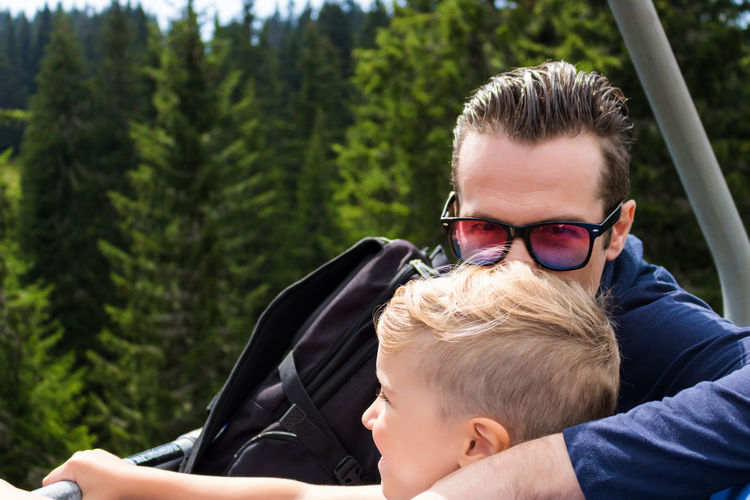 Happy father kissing his son while riding on chairlift and moving up the hill.