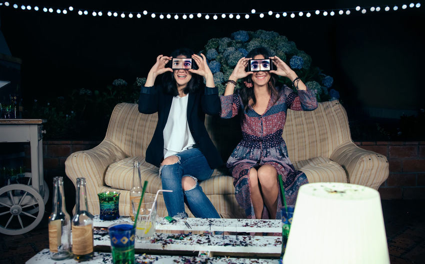 Portrait of funny young women couple holding smartphones over their faces showing male eyes in the screen on a outdoors party. Friendship and celebrations concept. Celebration Fun Funny Garland Horizontal Screen Sitting Woman Caucasian Covering Display Eyes Female Girl Grimace Male Night Outdoors Party Phone Smartphone Smiling Sofa Togheter Two People