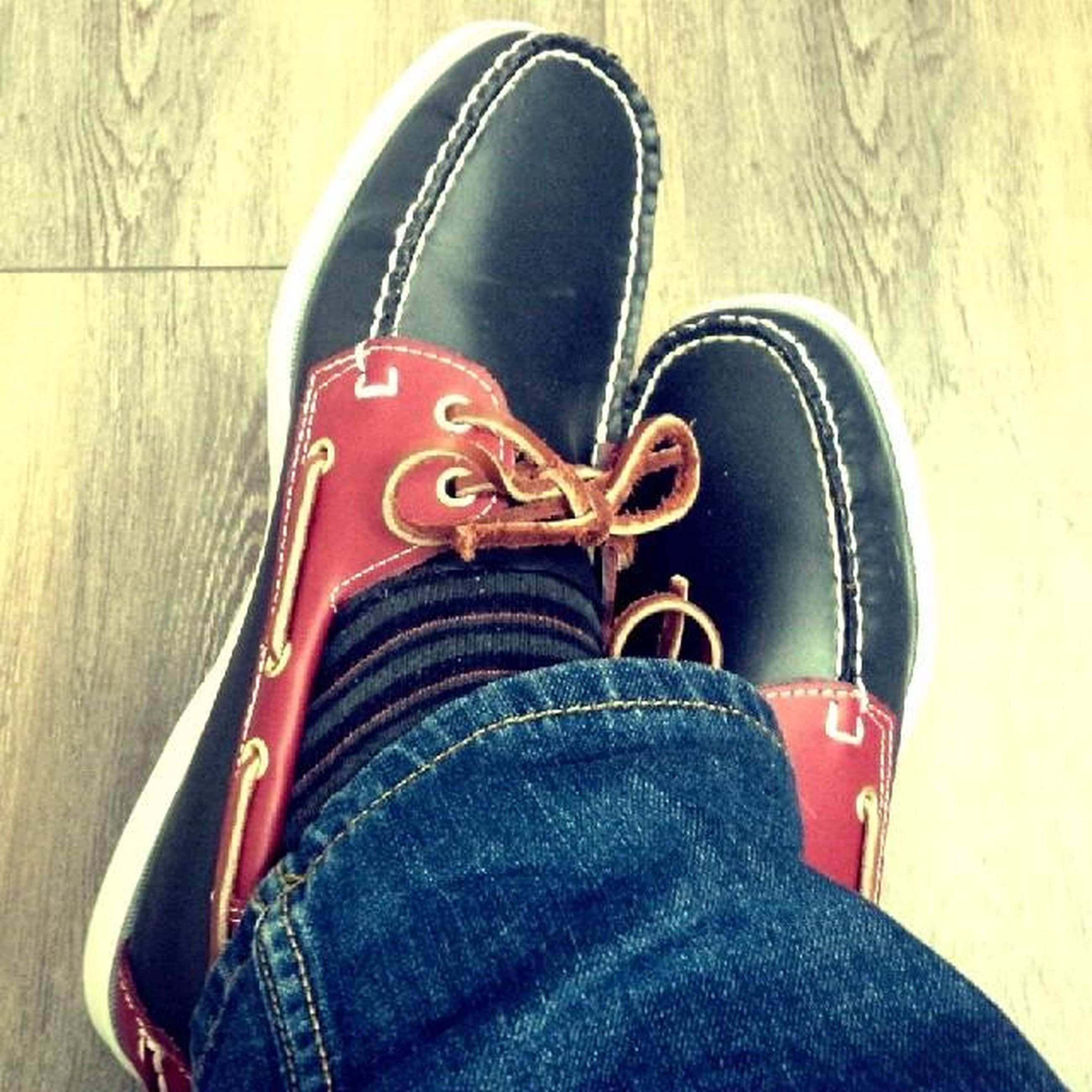 shoe, low section, person, jeans, footwear, high angle view, indoors, sitting, close-up, personal perspective, pair, men, canvas shoe, transportation, human foot, lifestyles, relaxation, black color