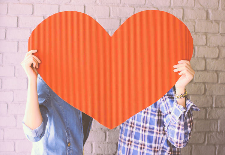Midsection of couple holding orange heart shaped paper on valentine day