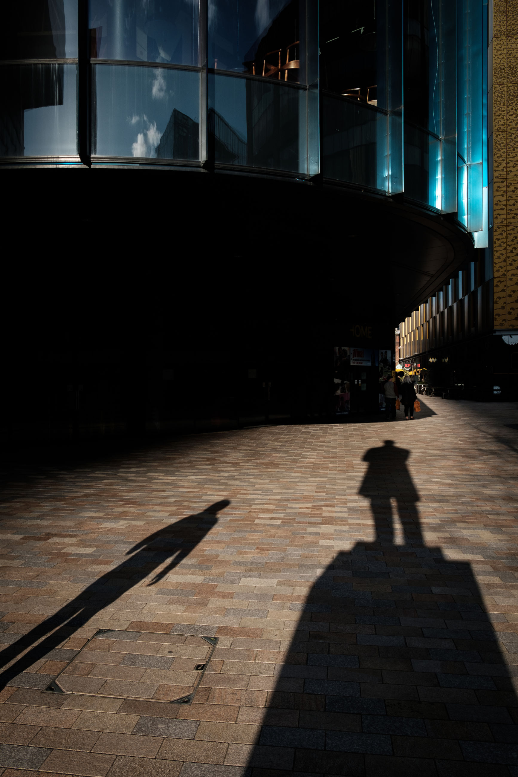 shadow, built structure, architecture, sunlight, building exterior, nature, one person, real people, building, city, lifestyles, footpath, walking, unrecognizable person, street, incidental people, outdoors, focus on shadow, paving stone