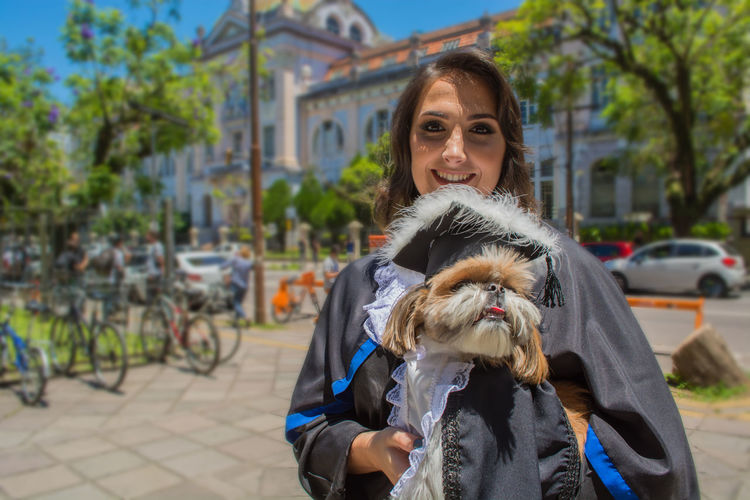 Portrait of woman wearing graduation gown while holding dog in city
