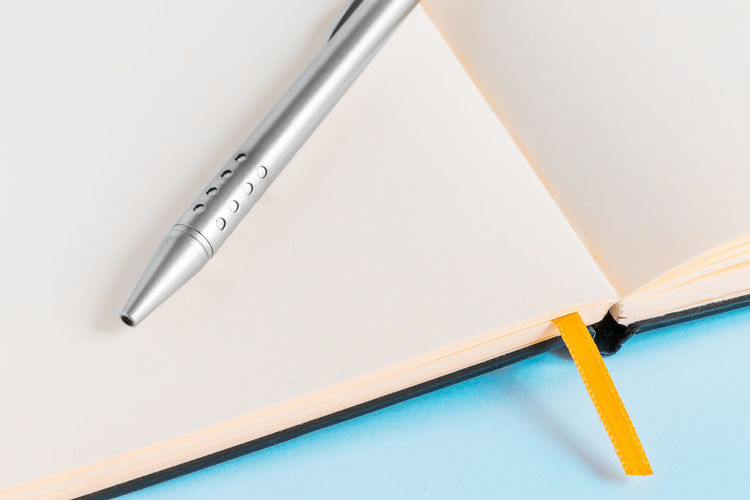 High angle view of pen on blank diary against blue background