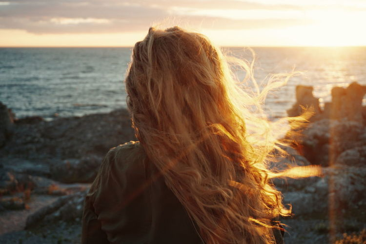 Rear View Of Woman Standing On Seashore At Sunset