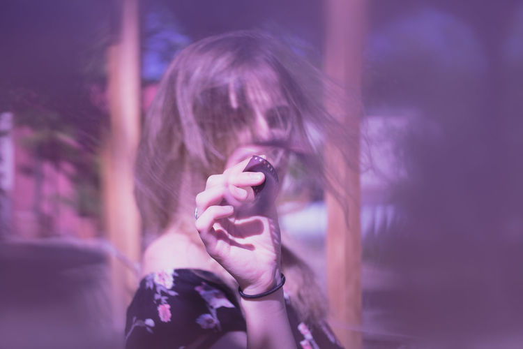 Portrait of woman holding film reel against sky