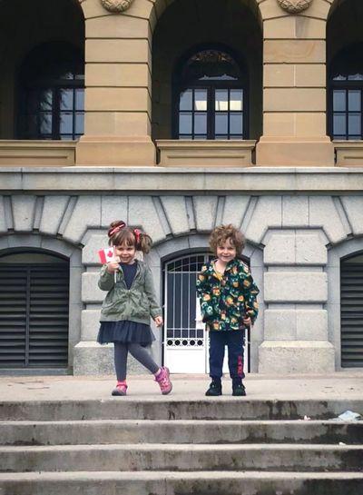 Full length of smiling siblings standing against building