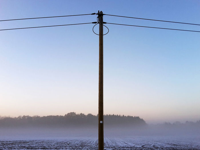 Electric post No. 10 Blue Sky Cable Countryside Day Electric Post Electricity  Electricity Pylon Fields Landscape Mist Nature No People Outdoors Power Line  Power Supply Rural Scene Sea Sky Sunset Telephone Line Winter Fresh On Market 2016