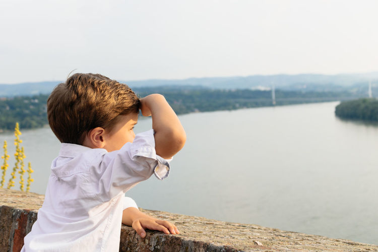 Side view of boy looking at river