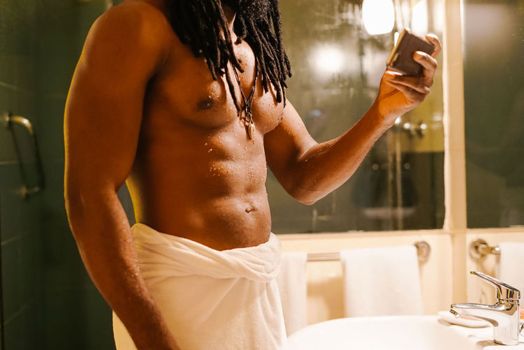 Midsection of shirtless man using phone while standing in bathroom