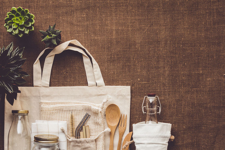 Directly above shot of bag with container and eating utensils on table