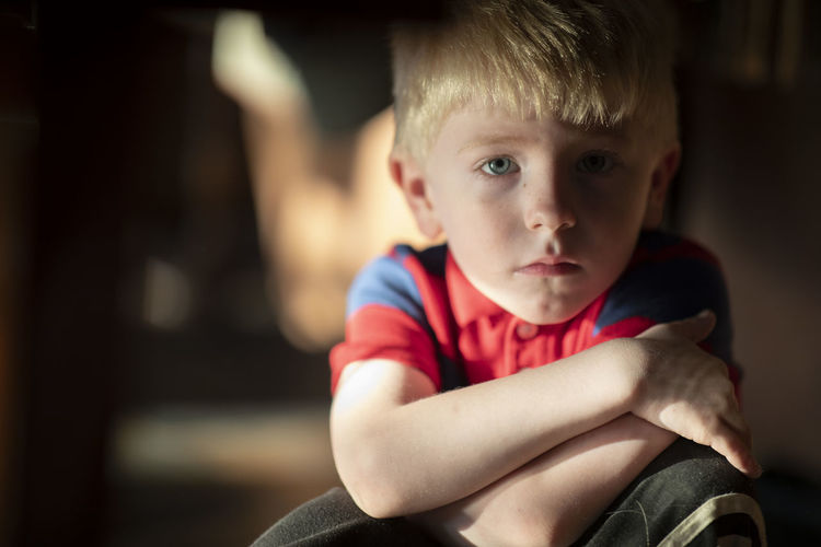 A four-year-old blonde haired blue eyed boy looks sadly into the camera. 85mm Blonde Portraits Blonde Hair Boys Child Childhood Close-up Contemplation Cute Depression - Sadness Emotion Focus On Foreground Front View Indoors  Innocence Looking At Camera Males  Men Offspring One Person Portrait Sadness Sitting