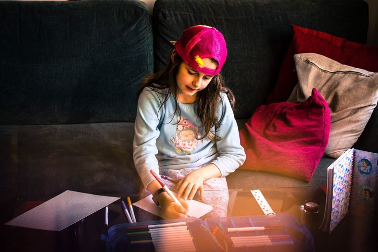 Girl drawing on book on table at home