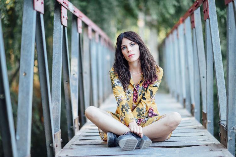 Portrait of young woman sitting on footbridge