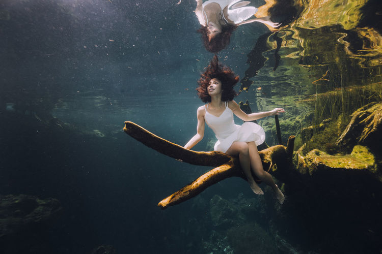 Woman sitting on branch underwater