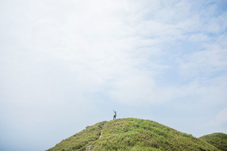 Man standing on hill against sky