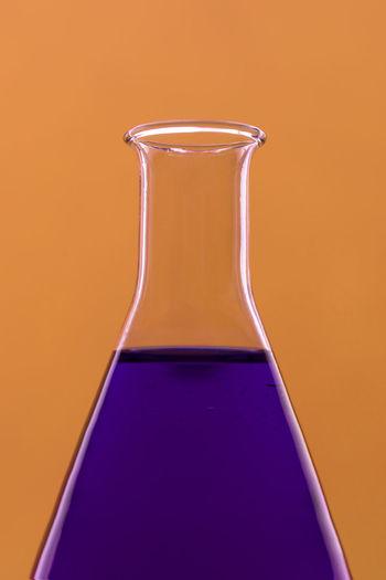 Close-up of purple liquid in flask against orange background