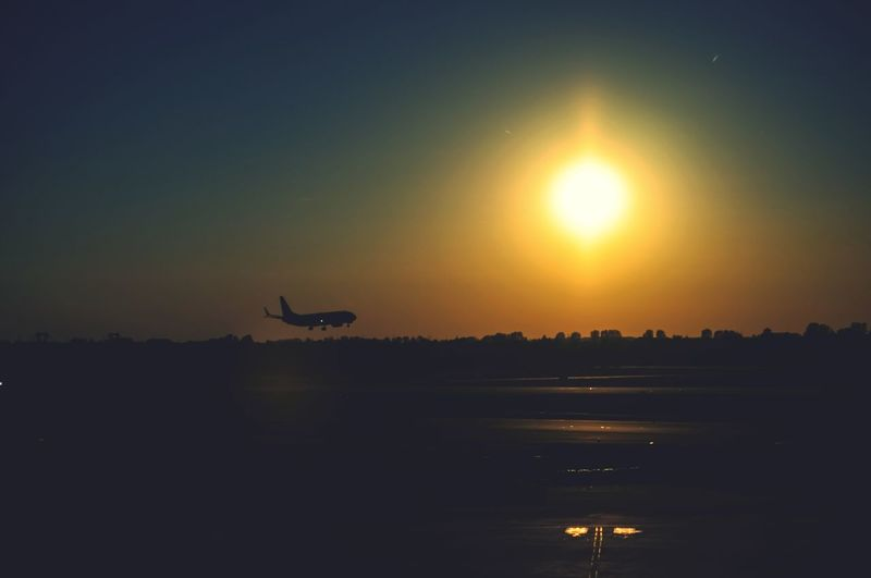 Airplane landing in the sunset Airport Travel Airplane Transportation Sky Sunset Sun Flying Scenics - Nature Silhouette No People Orange Color