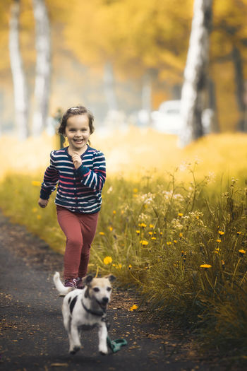 Smiling Girl With Dog Running On Road