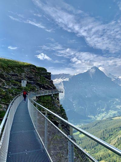 Footbridge over mountain against sky