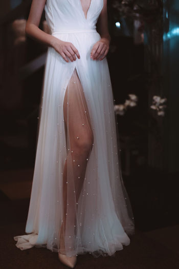 Cropped figure of model dressed in white long wedding dress.