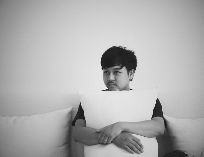 Man holding cushion while sitting on sofa at home