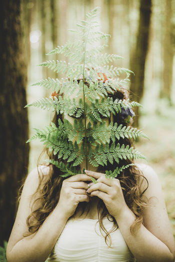 Close-Up Of Woman Holding Leaves In Forest
