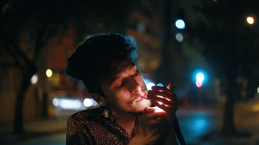 Portrait of young man using smart phone on street at night