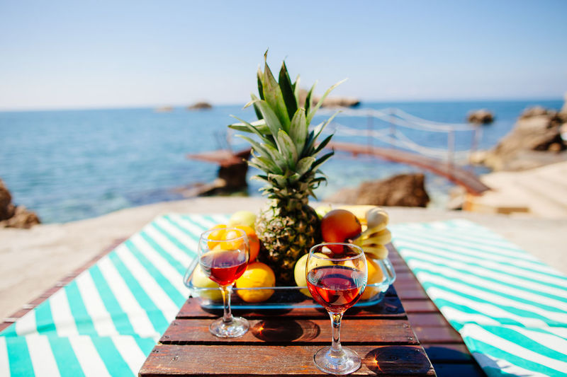 Close-up of drink and fruits on table against sea