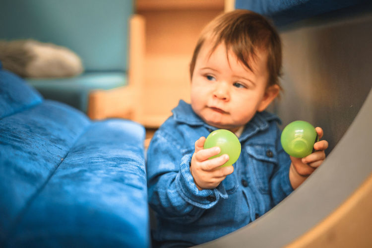 Baby Baby Boy Ball Blue Casual Clothing Childhood Close-up Cute Denim Home Interior Indoors  Lifestyles Multi Colored One Person Play Playing Real People Sitting