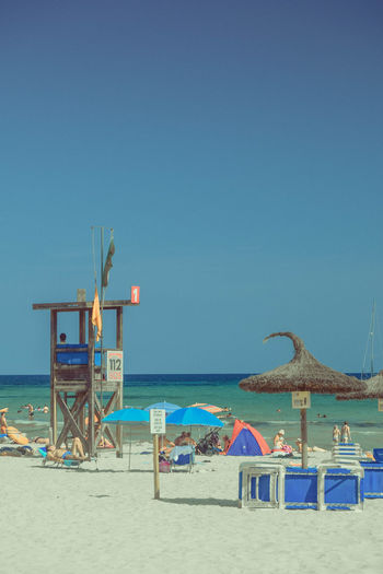 Sky Sea Water Beach Land Horizon Over Water Clear Sky Sand Nature Outdoors Parasols Beach Photography Horizon Blue Scenics - Nature Day Beauty In Nature Safety Copy Space Built Structure Tranquil Scene Copy Space