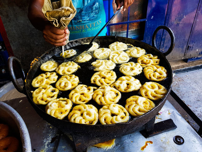 Jalebi an indian sweet dish being fried in sugar syrup in a large container Jalebi Business Concession Stand Day Food Food And Drink Freshness Fried Sweets High Angle View Holding Human Body Part Human Hand Jilipi Kitchen Utensil Men Occupation One Person Outdoors Preparation  Preparing Food Real People Street Food Sugar Syrup Sweet Dish  Vendor