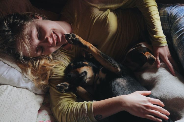 Young Woman With Dogs Relaxing On Bed At Home