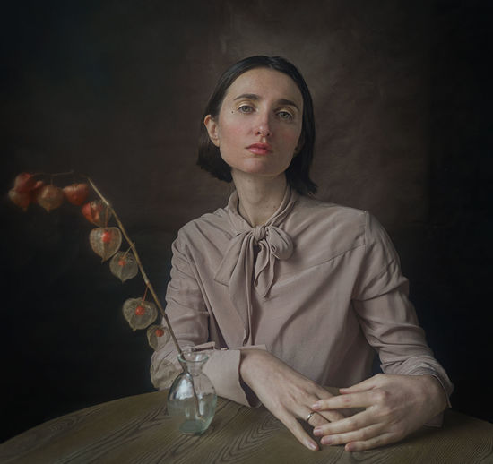 Portrait of young woman sitting at table