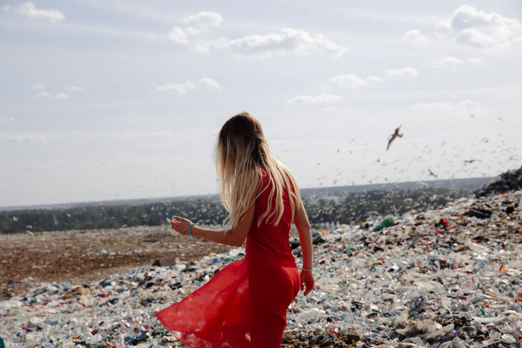 Woman walking amidst garbage against sky