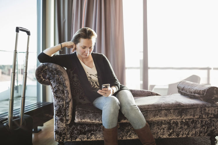 Young woman looking at camera while sitting on sofa
