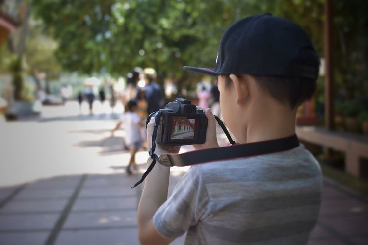 Rear view of boy photographing while standing on footpath in city