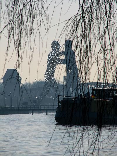 Molecule Men Amidst Spree River Against Sky